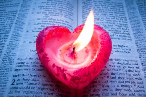 A candle shaped like a heart resting on a bible.