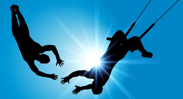 Trapeze acrobats in mid air