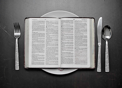 Dinner plate with cutlery and an open bible on top